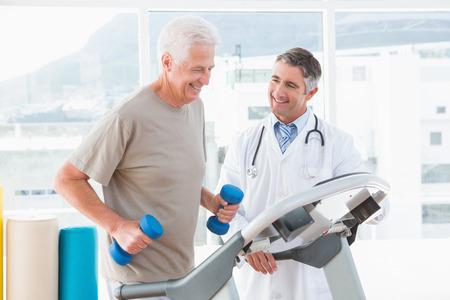 exercise room: Senior man on treadmill with therapist in fitness studio