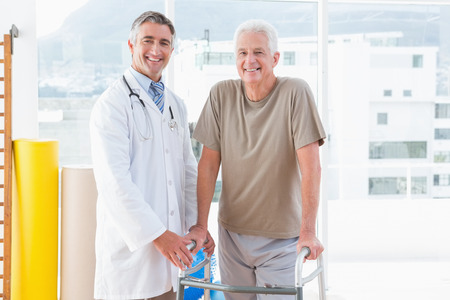 retirement happy man: Senior man with therapist smiling at camera in fitness studio Stock Photo
