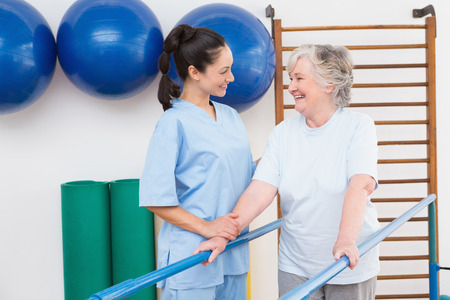 physical: Senior woman walking with parallel bars with therapist in fitness studio