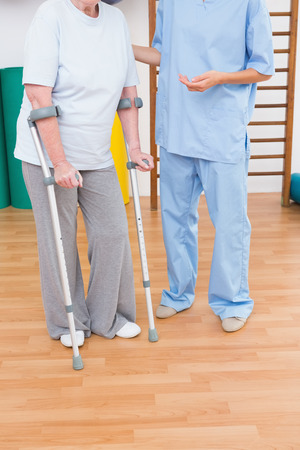convalescence: Therapist helping senior woman with scrubs in fitness studio Stock Photo