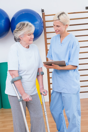 convalescence: Therapist and senior woman looking at clipboard in fitness studio