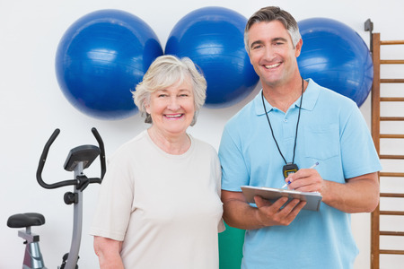 adult  body writing: Senior woman and trainer smiling at camera in fitness studio