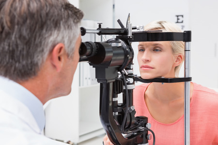 young adult women: Optometrist examining blonde woman in medical office