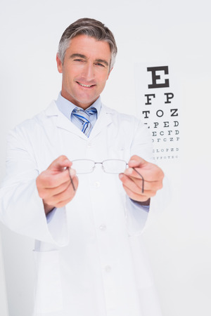 optometrist: Optometrist holding eyeglasses out in medical office