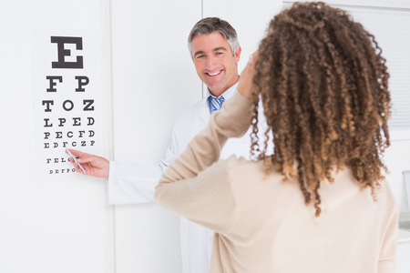 Woman doing eye test with optometrist in medical office photo