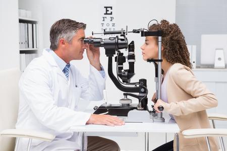 ojo humano: Mujer que hace el examen de la vista con un optometrista en el consultorio m�dico Foto de archivo