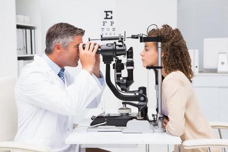 Mujer que hace el examen de la vista con un optometrista en el consultorio médico