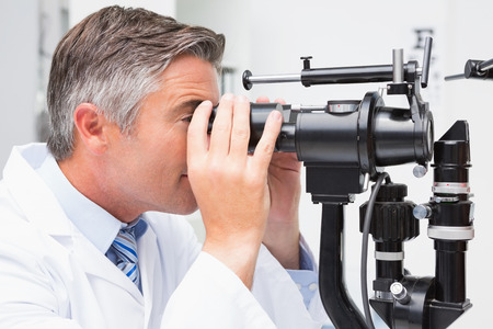 optical instrument: Optometrist looking in optical instrument in medical office
