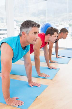 sport equipment: Group of men working on exercise mat in fitness studio