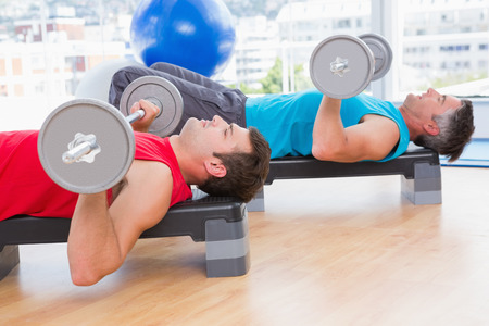 athletics training: Men lifting barbell in fitness studio Stock Photo