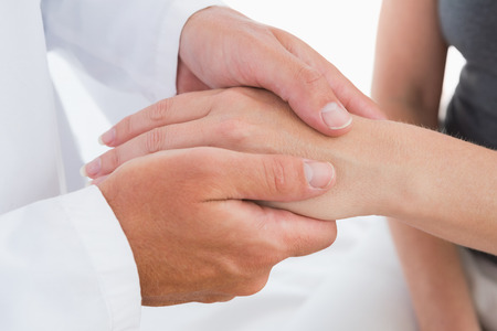 doctor examining woman: Doctor examining his patient hand in medical office