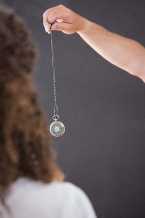 hypnosis: Woman being hypnotized with pendulum