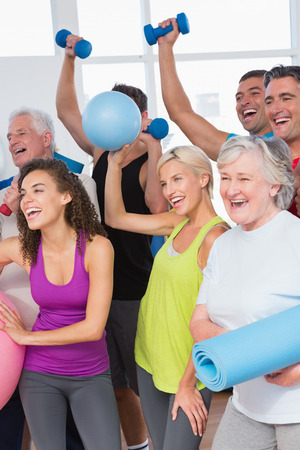 Cheerful friends with hands raised holding equipment in fitness studio Stock Photo