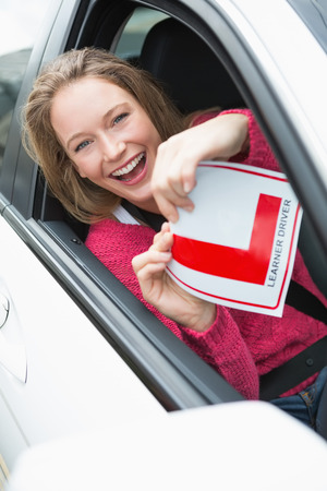 l plate: Learner driver smiling and holding l plate in her car Stock Photo