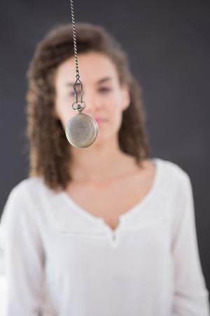 Mujer que es hipnotizado con péndulo Foto de archivo - 44809285