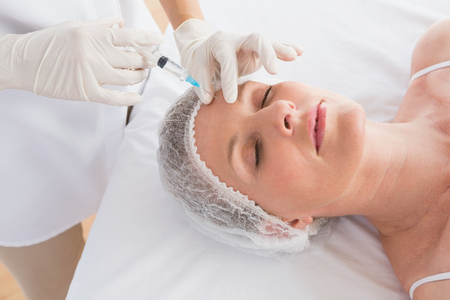 surgical cap: Woman receiving botox injection on her forehead in medical office