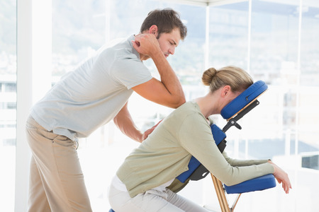 elbow chair: Woman having back massage in medical office Stock Photo