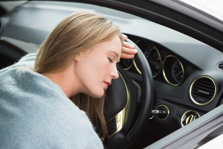 slumped: Tired woman asleep on steering wheel in her car Stock Photo
