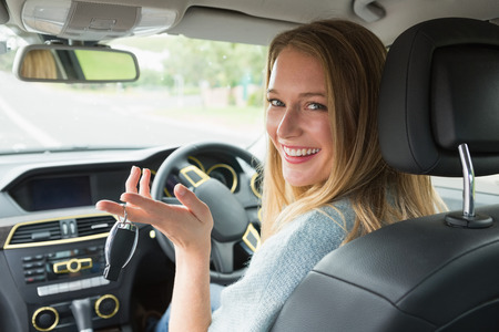 Young woman smiling at camera in her car photo