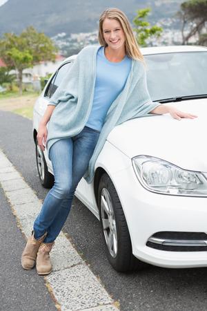 Young woman posing beside her car