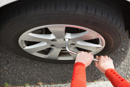 replacing: Woman replacing tire of her car