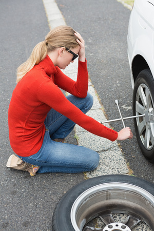 Annoyed woman trying to replace tire of her car Stock Photo