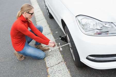 replacing: Young woman replacing tire of her car