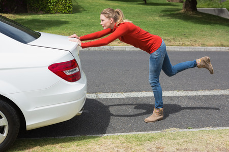 broken down: Young woman pushing her broken down car in the street Stock Photo