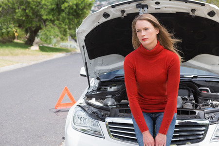 broken down: Annoyed young woman beside her broken down car in the street