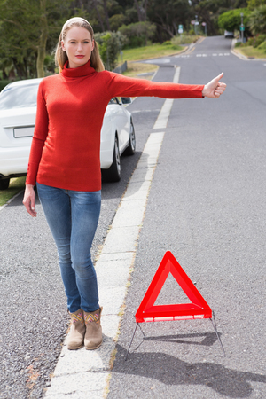 empty tank: Pretty woman hitch hiking in the street Stock Photo