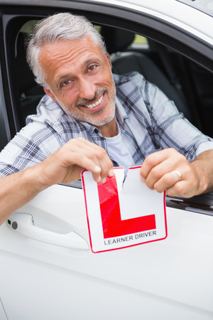 l plate: Driver smiling and tearing l plate in his car Stock Photo