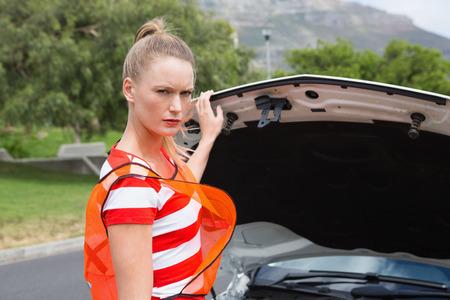 broken down: Worried young woman beside her broken down car in the street