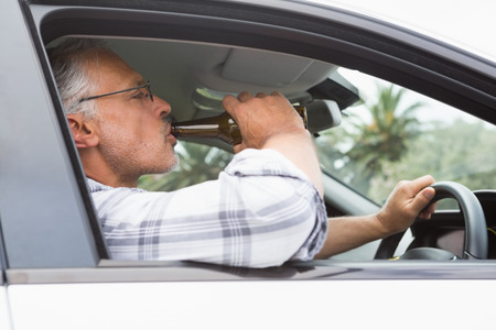 drinking driving: Man drinking beer while driving in his car