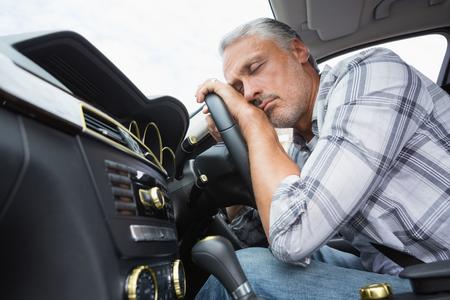 drunk driving: Drunk man slumped on steering wheel in his car