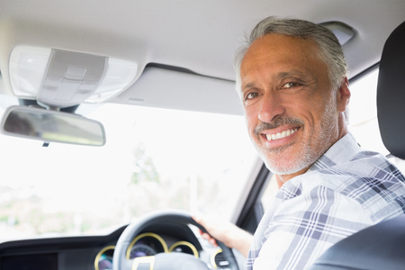man rear view: Man smiling while driving in his car