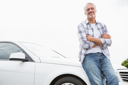 Man leaning on the bonnet of his car Stock Photo
