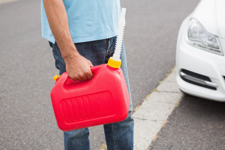 broken down: Man bringing petrol canister to a broken down car in the street