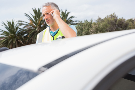 breaking down: Unsmiling man calling for assistance after breaking down on the road Stock Photo