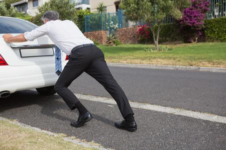 empujando: Hombre que empuja su coche averiado en la carretera Foto de archivo