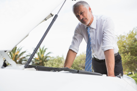 breaking down: Upset man checking his car engine after breaking down on the road Stock Photo