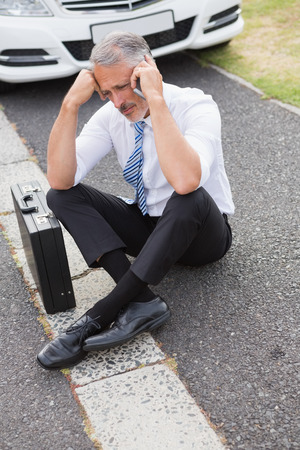 breaking down: Sad man calling for assistance after breaking down on the road Stock Photo
