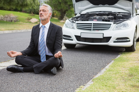 Businessman meditating after his car broken down on the road