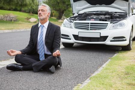 Zakenman mediteren nadat zijn auto afgebroken op de weg