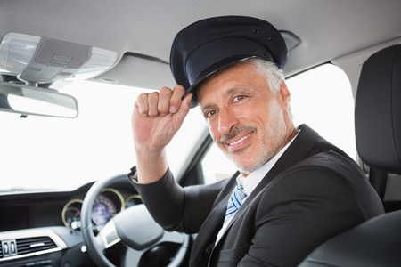 driver: Handsome chauffeur smiling at camera in the car