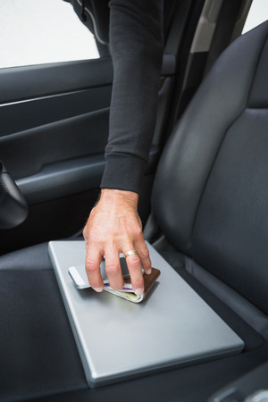 criminal activity: Thief breaking into car and stealing in broad daylight