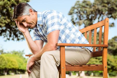desolaci�n: Malestar hombre sentado en el banco del parque en un d�a soleado