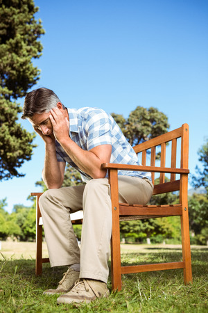 wistfulness: Upset man sitting on park bench on a sunny day