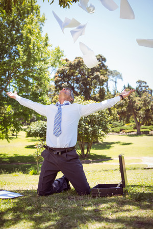 tossing: Businessman tossing papers in the park on a sunny day