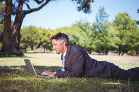 Businessman relaxing in the park on a sunny day photo