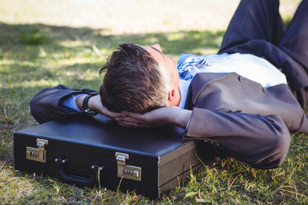sleeping businessman: Businessman relaxing in the park on a sunny day